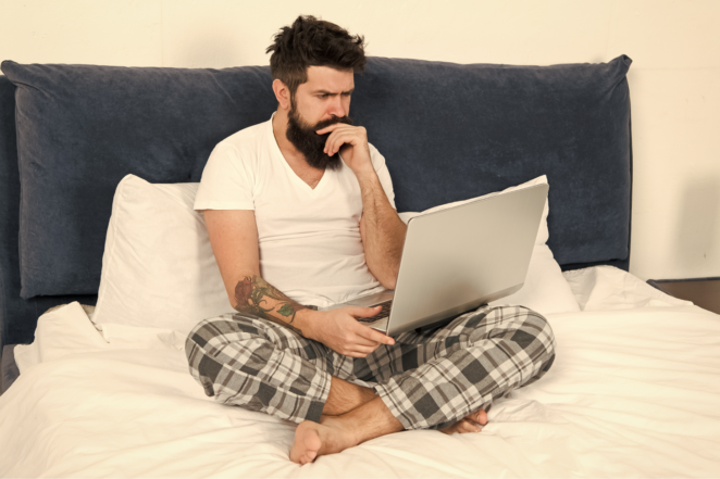 Man working remotely in bed